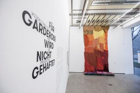 """Blick in den Eingangsraum. Im Hintergrund zu sehen: ROUGE, """"Can a Woman Make the Big Piece?"""", 2012"""